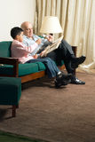 Grandfather and grandson sitting on the couch read Royalty Free Stock Images