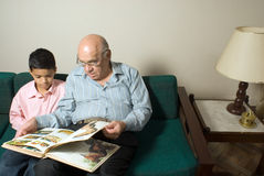Grandfather and grandson sitting on the couch read stock images