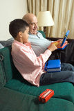 Grandfather and grandson sitting on a couch - Vert Stock Image
