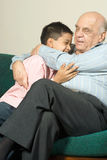 Grandfather and grandson sitting on couch - Vertic Stock Photo