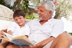 Grandfather And Grandson Sitting In Garden Reading Book� Stock Image