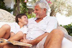 Grandfather And Grandson Sitting In Garden Reading Book� Royalty Free Stock Image