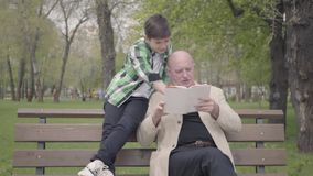 Grandfather and grandson sitting in the park on the bench, old man reading the book for the boy. The child standing with