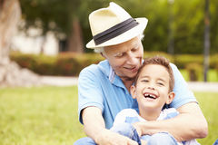 Grandfather And Grandson Sitting In Park Together Stock Photography