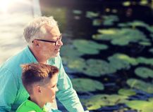 Grandfather and grandson sitting on river berth royalty free stock photo