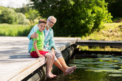 Grandfather and grandson sitting on river berth Stock Image