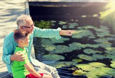 Grandfather and grandson sitting on river berth royalty free stock images