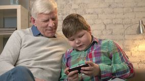 Grandfather and grandson sitting on the sofa using a smartphone, speaking, a fat child is playing on a smartphone. Young. Fat boy and grandfather. Home comfort stock footage