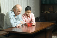 Grandfather and grandson sitting at the table with Stock Photography