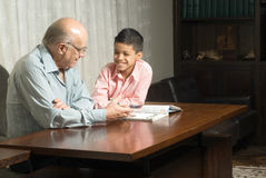 Grandfather and grandson sitting at table with boo Stock Images