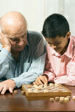 Grandfather and grandson sitting at the table play Royalty Free Stock Photos