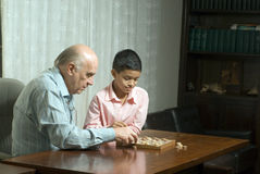 Grandfather and grandson sitting at table playing Stock Photos