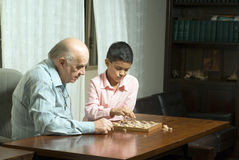 Grandfather and grandson sitting at table playing Royalty Free Stock Photos