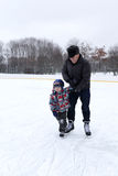 Grandfather and grandson at the skating rink Stock Photos