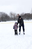 Grandfather with grandson at the skating rink Royalty Free Stock Images