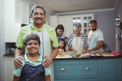 Grandfather and grandson smiling at camera while family members preparing dessert in background royalty free stock photos
