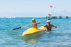 Grandfather and grandson smiling little baby boy in green baseball cap kayaking at tropical ocean sea in the day time. Positive h. Uman emotions, feelings, joy stock photos