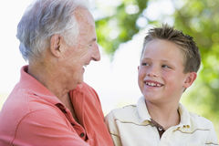 Grandfather and grandson smiling outdoors. Royalty Free Stock Image