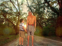 Grandfather and grandson standing at the forest Stock Photos