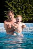 Grandfather and grandson swim Stock Photography