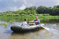 Grandfather with grandson swim in a rubber boat on the river. Stock Photos