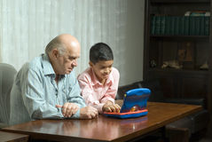 Grandfather and grandson on table playing - Horizo Stock Photo