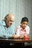 Grandfather and grandson at table w toy-Vert Royalty Free Stock Photos