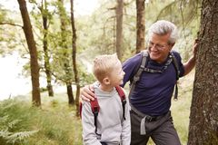Grandfather and grandson taking a break while hiking together in a forest, close up, looking at each other stock image