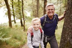 Grandfather and grandson taking a break while hiking together in a forest, close up, smiling to camera stock photos