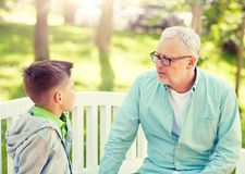 Grandfather and grandson talking at summer park stock photos