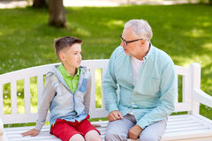 Grandfather and grandson talking at summer park Stock Photography