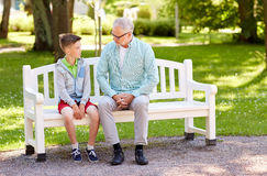 Grandfather and grandson talking at summer park Stock Image