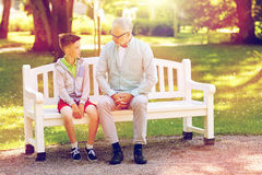Grandfather and grandson talking at summer park. Family, generation, communication and people concept - grandfather and grandson talking at summer park Stock Images