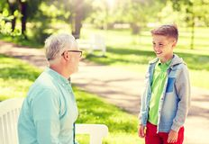 Grandfather and grandson talking at summer park royalty free stock photo