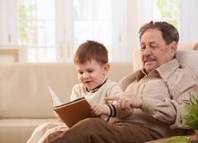 Grandfather and grandson together at home stock image