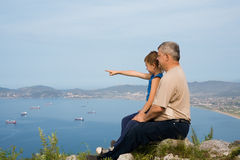 Grandfather and grandson at the top of the mountain. Stock Photo