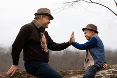 Grandfather and grandson on a tree. Royalty Free Stock Image