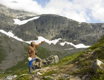 Grandfather and grandson trekking. Boy and grandfather climbing a mountain, pointing towards the top. Vengedalen, Rauma, Norway Stock Images