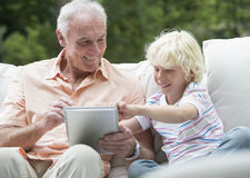Grandfather and grandson using digital tablet on outdoor sofa Royalty Free Stock Photo