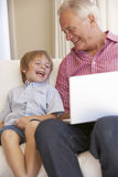 Grandfather And Grandson Using Laptop At Home Royalty Free Stock Photography