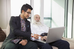 Grandfather and grandson using laptop in living room Royalty Free Stock Photo