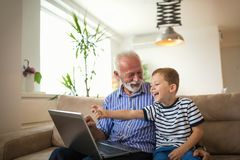 Grandfather and grandson using laptop Stock Photos