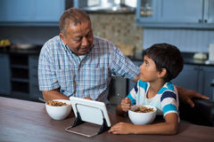 Grandfather and grandson using tablet computer during breakfast Royalty Free Stock Photo