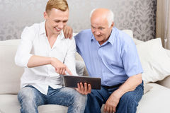 Grandfather and grandson using tablet together Stock Photos