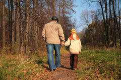 Grandfather and the grandson walk on wood Royalty Free Stock Image