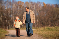 Grandfather and the grandson walk on wood Royalty Free Stock Photography