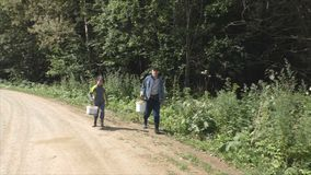 Grandfather and grandson walking along the road stock video footage