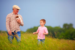 Grandfather with grandson walking through the summer field Stock Images
