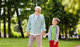 Grandfather and grandson walking at summer park Royalty Free Stock Photos