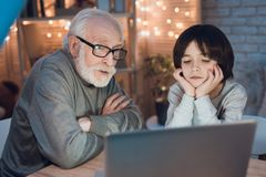 Grandfather and grandson are watching movie on laptop at night at home. Grandfather and grandson are watching movie on laptop at table at night at home Stock Photos